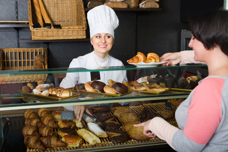 gladly: smiling brunette woman gladly choosing pastry in cafeteria store window Stock Photo