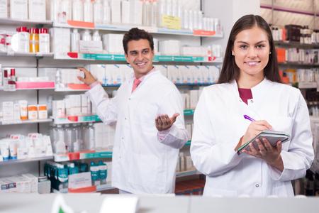 Portrait of two friendly pharmacists in uniform working in modern pharmacy