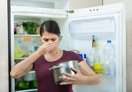 foul: Angry and upset housewife looking into a pot with a foul meal Stock Photo