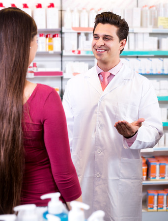 Cheerful experienced pharmacist counseling female customer Stock Photo