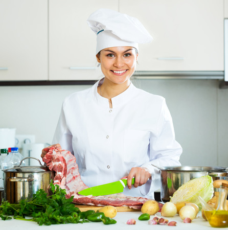 Beautiful female chef working with pork ribs in kitchen Stock Photo