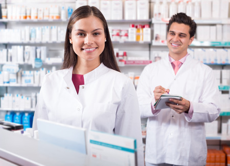 Professional smiling russian pharmaceutists at reception of drugstore ready to help Stock Photo