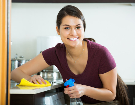 Portrait of happy brunette dusting in kitchen