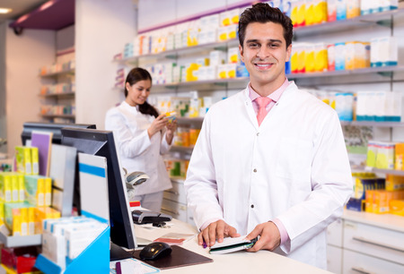 Portrait of smiling pharmacist and assistant working at farmacy reception