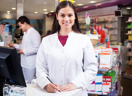 Cheerful pharmacist standing at a pay desk and a pharmacy technician helping