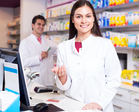 Portrait of happy pharmacist and assistant working at farmacy reception Stock Photo