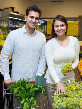 citrus family: Happy young spouses choosing fruits in grocery store indoors