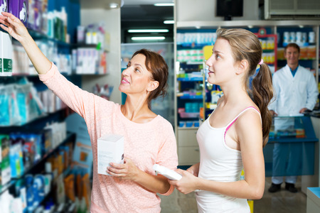 drug store: Portrait of positive woman with daughter teenager shopping healthcare products in drug store