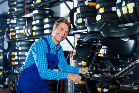 tire fitting: cheerful smiling mature professional mechanic man examining motorcycle in shop Stock Photo