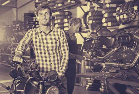 tire fitting: Portrait of young cheerful glad smiling customer choosing new motorbike in workshop Stock Photo