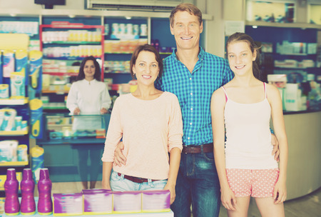 three shelves: Positive family of three persons standing in pharmacy among shelves with goods