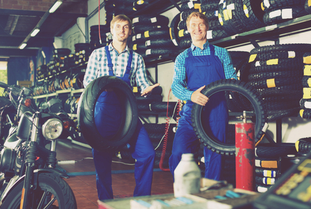 tire fitting: Two cheerful male professionals standing with new tires for motorcycle in hands in shop