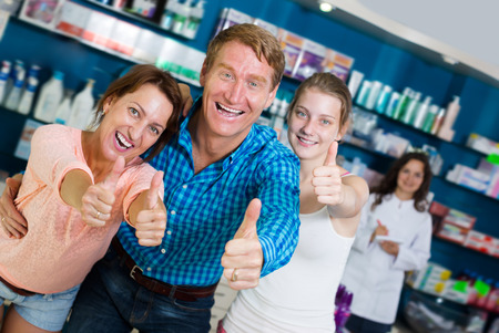 three shelves: Cheerful family of three persons holding thumbs up in pharmacy among shelves with goods