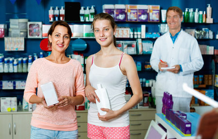 buying questions: Smiling  charming woman with girl teenager packing body care goods in pharmaceutical store Stock Photo