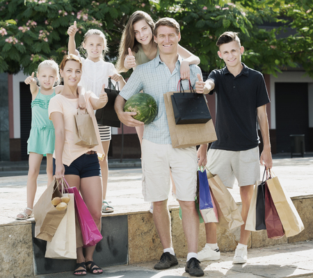 gladly: Cheerful young parents with four kids gladly shopping in town