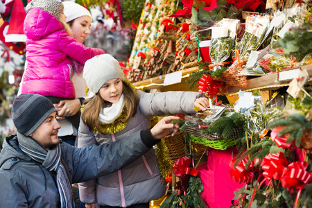 Ordinary family with little girls standing at coniferous souvenirs counter at fair. Focus on man and child in gray clothes