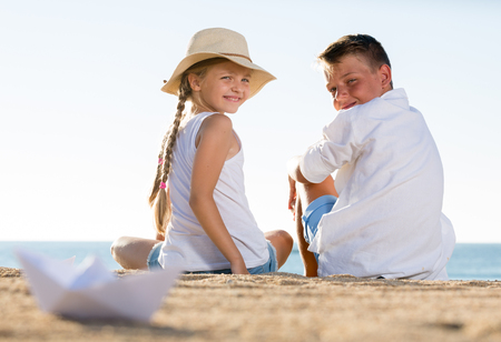 portrait of boy and girl in elemenary school age sitting together on sandy beach