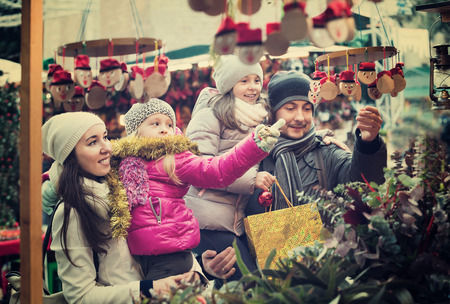 ittle: Happy cheerful family of four buying Caga Tio at Christmas market. Focus on woman and ittle girl