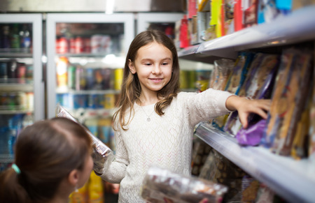 ordinary woman: Ordinary woman and little girl buying sweets at supermarket