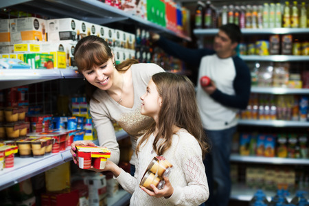 clase media: Ordinary middle class family buying sweet pudding in local store. Focus on girl