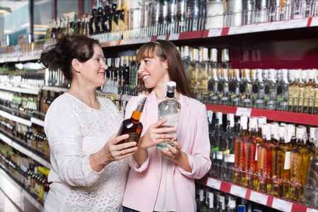 middle class: Ordinary happy mature woman and her adult daughter buying strong alcohol Stock Photo