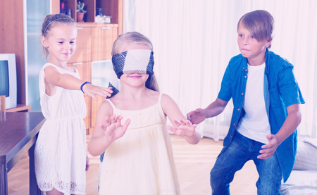 blindfolded: Blindfolded child catching other players in Kagome at home