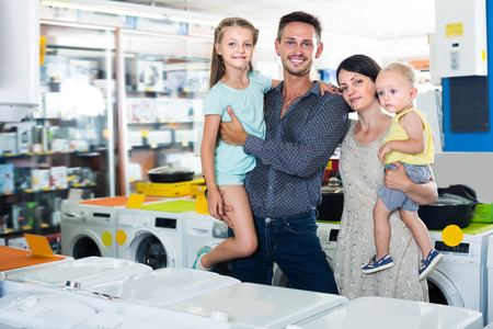 niños de compras: Young family with two children shopping together in shop of household appliances