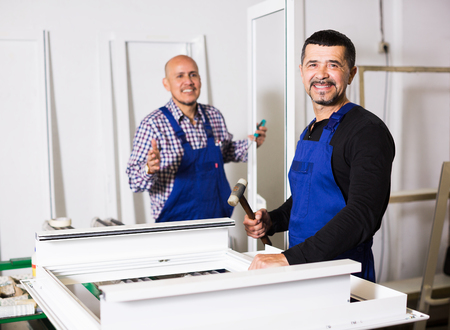 glasswear: Professional labours produce PVC profiles and windows at factory Stock Photo