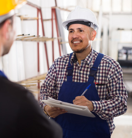 smiling american mechanical engineer inspecting the work of labour at modern factory Stock Photo