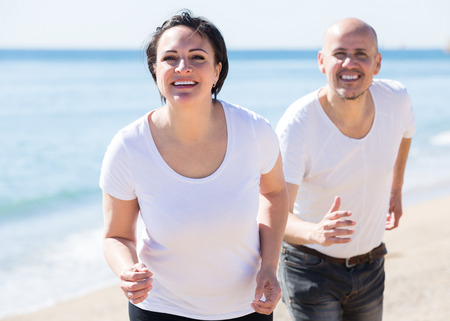 2 50: Cheerful adult man and woman jogging together in the good weather. Focus on woman