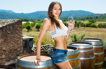 Young cheerful woman standing among wine woods with glass of sparkling wine outdoors
