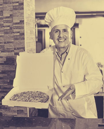 fast food restaurant: Cheerful  positive mature man cook giving freshly made pizza in fast food restaurant