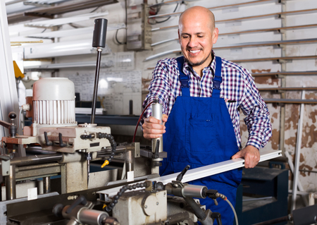 toiling: Positive smiling middle-aged man in coverall toiling on a machine in PVC shop