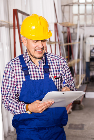 erector: adult american  male surveyor in coverall doing checkup and filling papers