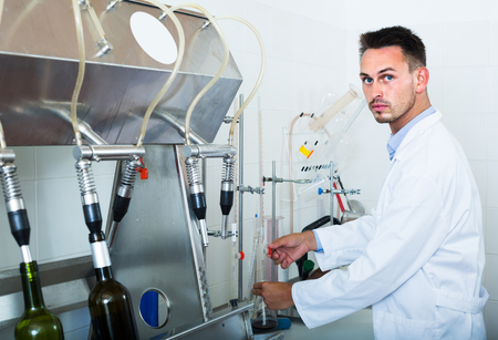 russian man: attentive young russian man making tests in wine manufactory laboratory