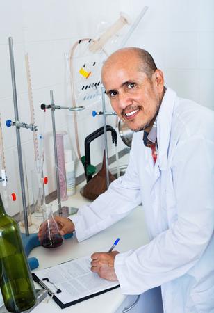 diligente: diligente atento sonriente hombre maduro que trabaja en la calidad de los productos en el laboratorio de la bodega