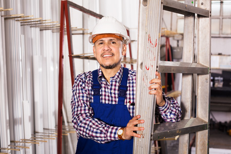 erector: Positive male installer in coverall working at construction site and smiling