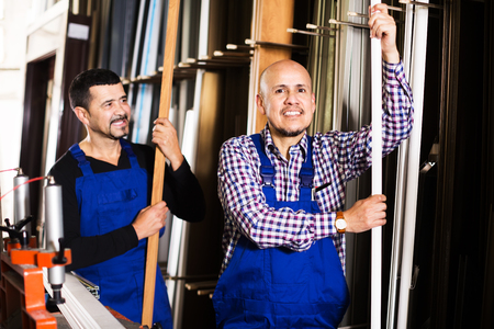 finished good: Two positive labours inspecting PVC manufacturing output in workshop Stock Photo
