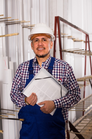 toolroom: Middle age workman in helmet with documents at workshop Stock Photo