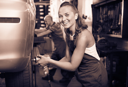 diligente: Young diligent smiling  mechanic woman working on wheel equilibrium control machinery in car service Foto de archivo