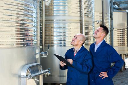 empleados trabajando: Dos empleados de la bodega masculinos positivos de trabajo y tomando notas en la sección segunda fermentación Foto de archivo