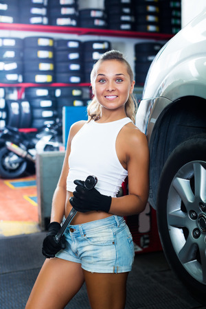 Positive young mechanic woman working on car wheel in service point