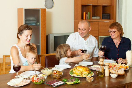 multigeneration: Portrait of happy multigeneration family  eating chicken at home together