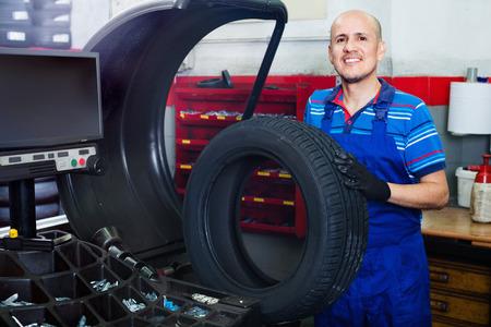 equilibrium: Mature diligent mechanic man having car wheel on equilibrium control machinery in car service