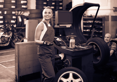 wheel balancing: Young european female technician standing with wheel balancing machinery at auto workshop