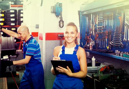 Giovane sorridente spagnolo tecnico femminile in tuta in possesso di appunti in officina auto