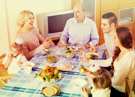 three generations of women: Cheerful sunday dinner in the bosom of family indoor Stock Photo