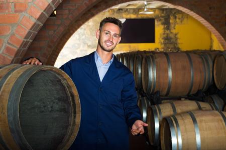 aging american: portrait of smiling male wine maker in coat working in winery cellar