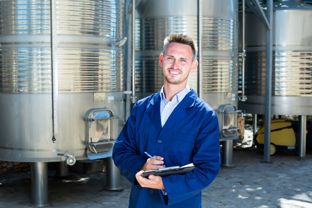 fermentation: Portrait of man winery worker standing on wine factory in secondary fermentation section Stock Photo