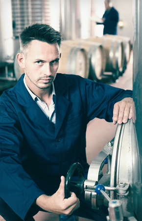 young man professional machinery operator working in secondary fermenting section on winery